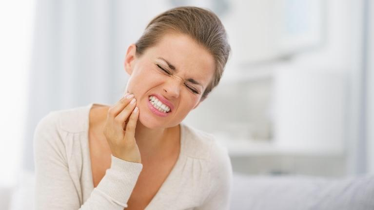 Woman Holding Tooth In Pain | Emergency Dental Care